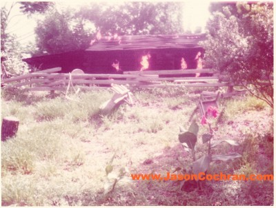 This burning cabin appeared after Fort Langhorn on the Rivers of America, Magic Kingdom, Walt Disney World. The gag was that Indians had sacked it and killed a white men doing it. This bit of racism was removed fully by 2005 and now the cabin sits silent. July 1973